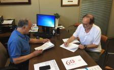 Andreu González i Jordi Pousa, signant el conveni